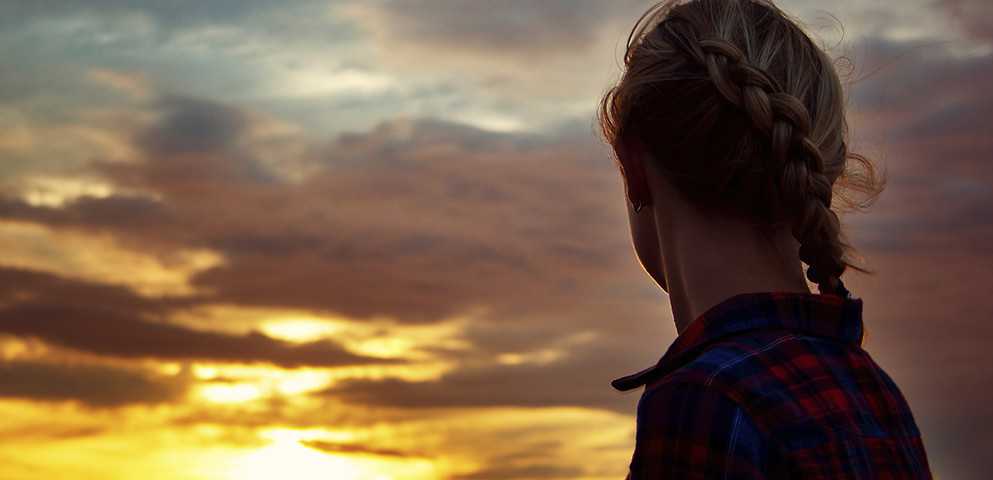 This is a decorative image. A woman turned away from the camera to look at a sunset.