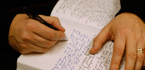 This image is decorative. A closeup of two hands, one writing in a journal.